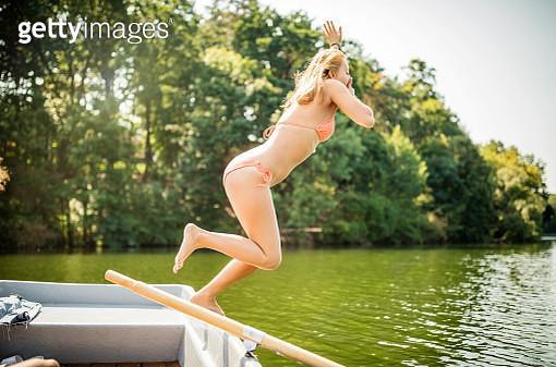 Young woman in bikini jumping into the lake from boat. Female in swimwear taking a plunge in lake water. - gettyimageskorea