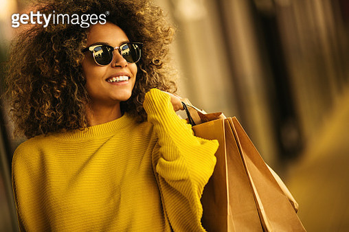 Beautiful mixes race woman holding shopping bags and smiling - gettyimageskorea