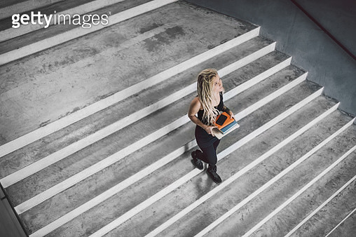 young tattooed woman walking in modern architecture - gettyimageskorea