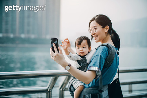 Mother and cute baby girl taking selfie joyfully with smartphone by the harbour in city - gettyimageskorea