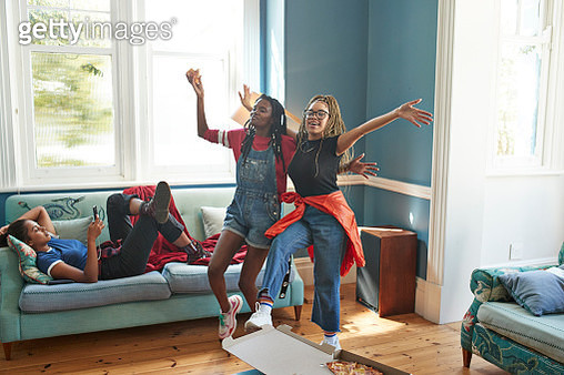 Happy friends dancing together while woman using phone on sofa at home - gettyimageskorea