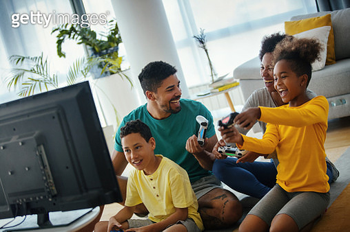 Closeup side view of a young african american family with two children spending time at home during coronavirus pandemic in 2020. They are playing some video games in the living room.  For later use this is a quite useful family lifestyle content. - gettyimageskorea