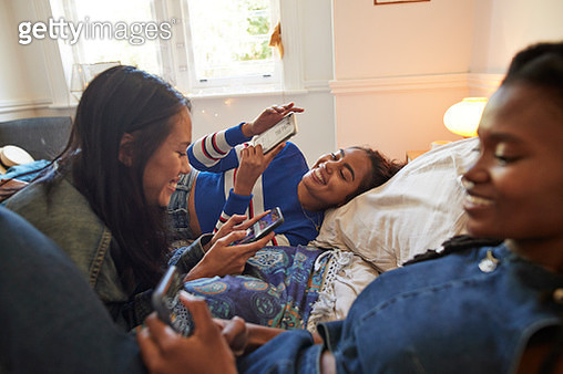 Smiling young female friends enjoying slumber party while using smart phones on bed at home - gettyimageskorea
