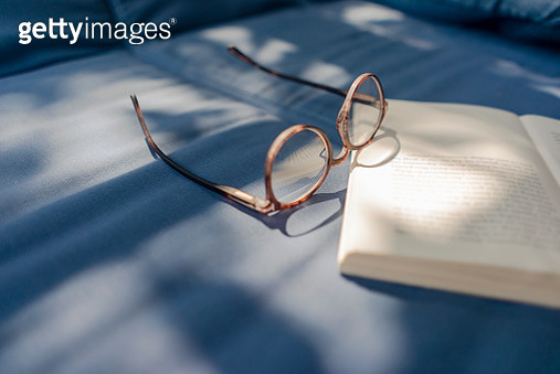 Eyeglasses and book lying on couch - gettyimageskorea