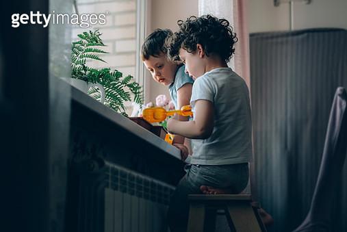 Two little kids planting seeds in their indoor window garden. - gettyimageskorea
