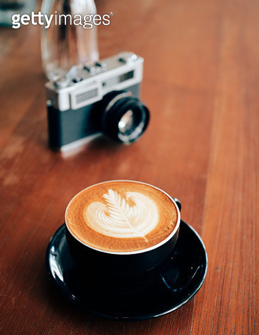 High Angle View Of Coffee Cup With Camera On Wooden Table In Cafe - gettyimageskorea