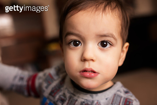 Portrait of a Serious Brunette Male 2 Year Old Toddler Who Has a Fever and is Sick - gettyimageskorea