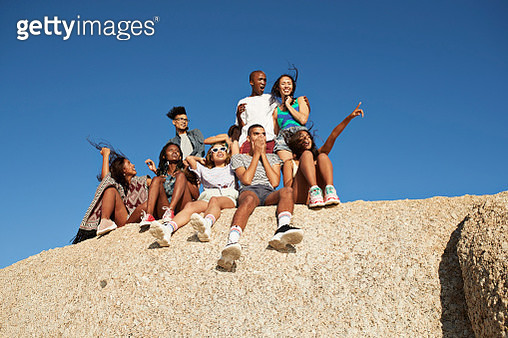 Cheerful friends sitting together on rock - gettyimageskorea
