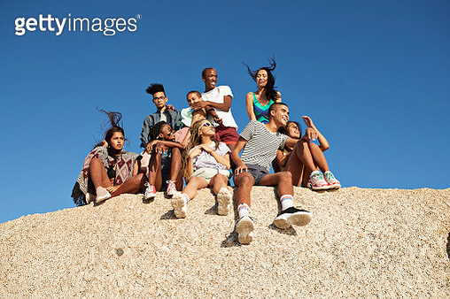 Low angle view of multi-ethnic friends sitting together on rock against clear blue sky - gettyimageskorea