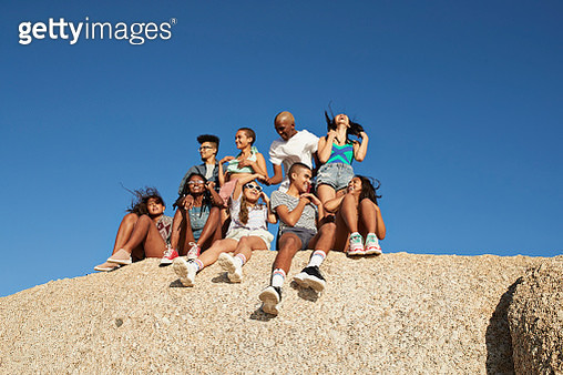 Happy multi-ethnic friends sitting together on rock - gettyimageskorea