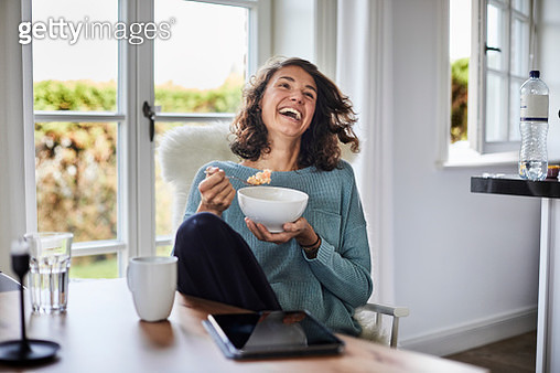 Happy woman having breakfast at dining table - gettyimageskorea
