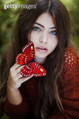Portrait of teenage girl (16-17) holding red artificial butterfly - gettyimageskorea