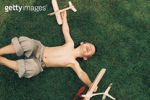 Young Boy Lying in the Grass With His Eyes Closed Playing With Two Toy Aircrafts - gettyimageskorea