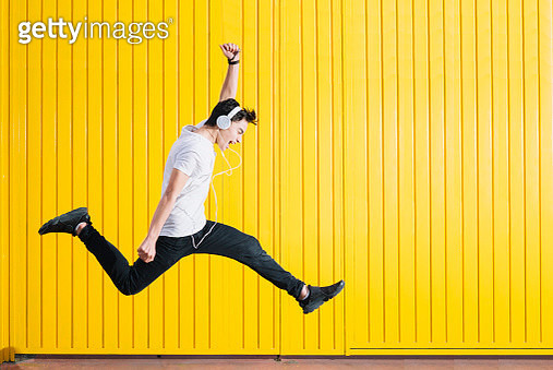 Teen with headphones and smartphon listening to music jumping - gettyimageskorea