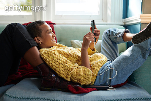Smiling woman text messaging on smart phone while leaning on friend's leg in living room - gettyimageskorea