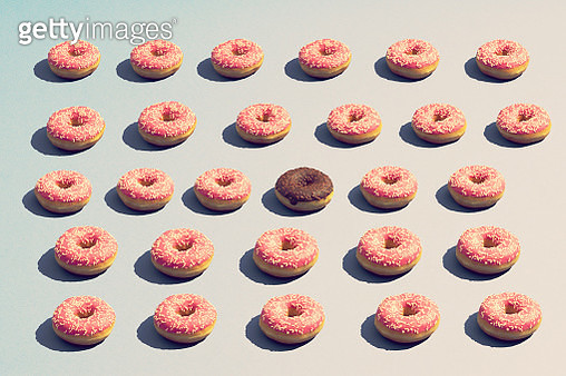 A chocolate donut amongst a big group of pink donuts - gettyimageskorea