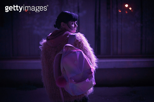 Rear View Of Woman Carrying Backpack Standing In City At Night - gettyimageskorea
