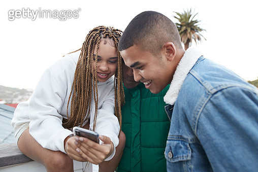 Young woman with braided hair showing smart phone to male friends at terrace against clear sky - gettyimageskorea
