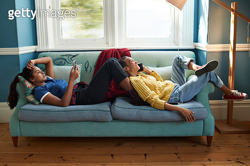 Full length of female friends using mobile phones while resting on sofa together at home - gettyimageskorea