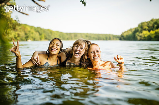 Portrait of three young women together in lake. Group of young female friends enjoying swimming together in lake. - gettyimageskorea
