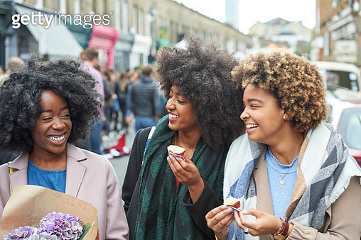 Friends laughing and eating cupcakes at flower market. - gettyimageskorea