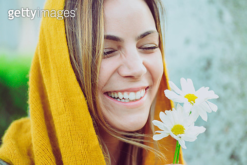 Young woman, scarf and daisy - gettyimageskorea