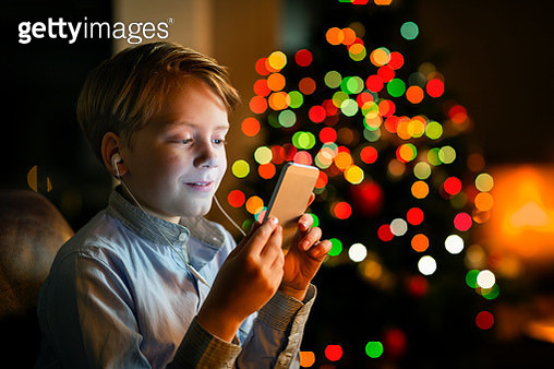 Boy listening music on smartphone during Christmas - gettyimageskorea