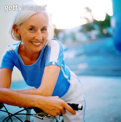 Portrait of an elderly woman smiling leaning forward on bicycle handlebars - gettyimageskorea