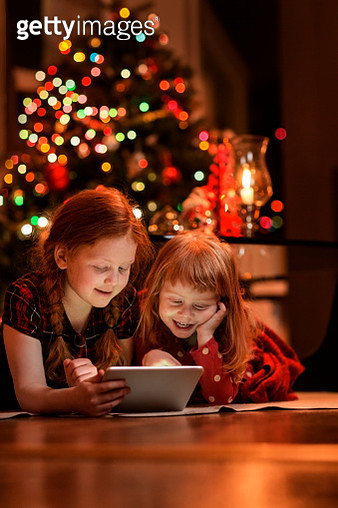Sisters using tablet PC on floor during Christmas - gettyimageskorea