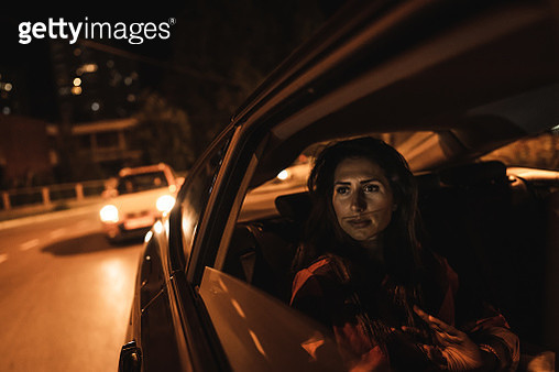 Woman sitting on back seat and looking through window - gettyimageskorea