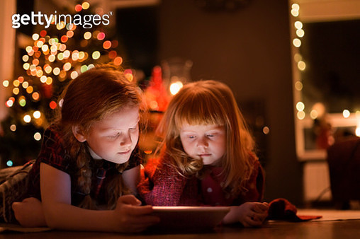 Girls watching tablet PC at home during Christmas - gettyimageskorea