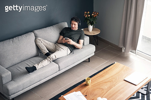High angle shot of a mature man using a cellphone while relaxing at home - gettyimageskorea