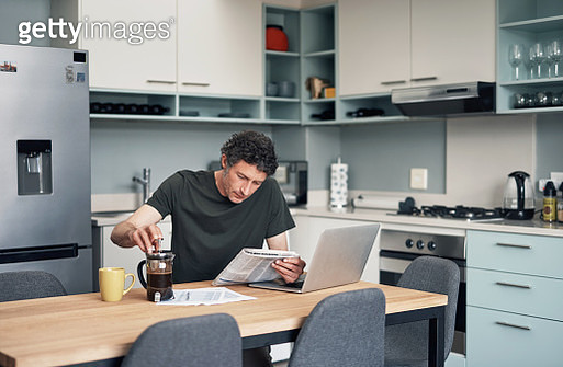 Shot of a mature man drinking coffee while reading a newspaper at home - gettyimageskorea