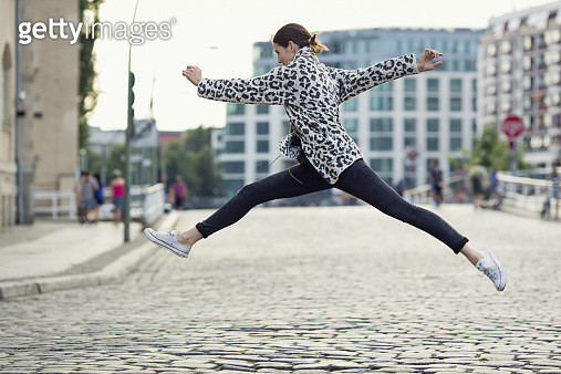 Woman jumping like a dancer performing a grand jeté, trying to go over the longest distance possible, with her arms open. She is joyfully jumping over a paved open street, in front of blurred city background and an open sky. - gettyimageskorea