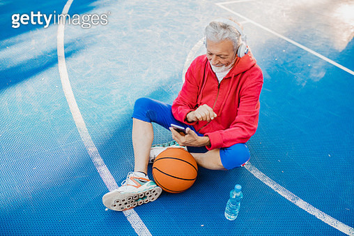 Senior man on the basketball field listening to music - gettyimageskorea