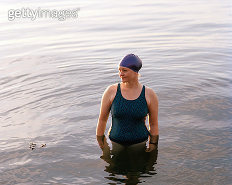 Female swimmer standing in the sea at sunset - gettyimageskorea
