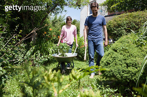 Couple with wheelbarrow gardening together - gettyimageskorea