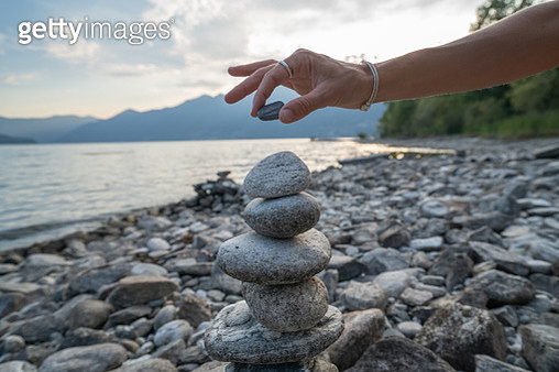 Detail of person stacking rocks by the lake - gettyimageskorea