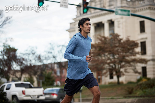 Young Latino man in blue sweatshirt runs by small town courthouse - gettyimageskorea