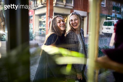 Two happy young women behind shop window - gettyimageskorea