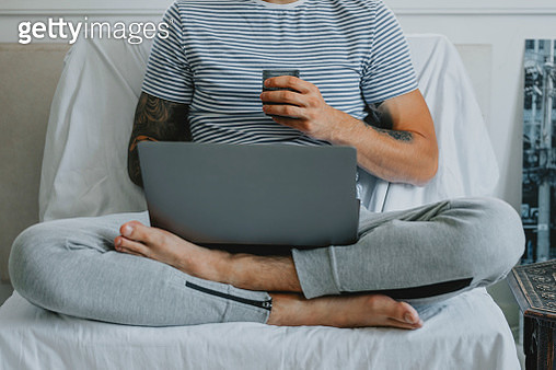 Working at Home: Anonymous Young Businessman Attending an Online Conference while Sitting and Drinking Coffee in his Living Room - gettyimageskorea