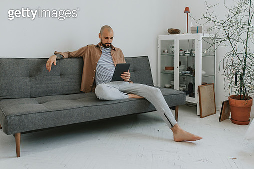 Relaxing at Home: Young Man Chatting on Social Media on his Tablet PC while Sitting on a Couch in his Living Room - gettyimageskorea