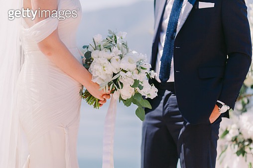 Midsection Of Bride Holding Bouquet While Standing By Groom - gettyimageskorea