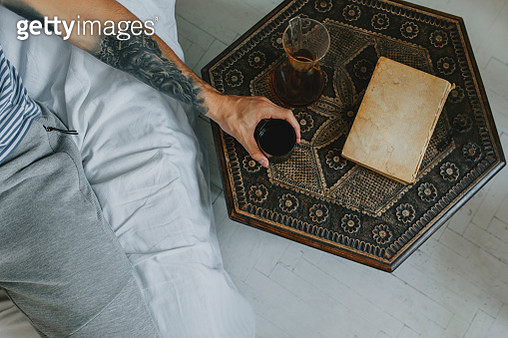Mornings at Home: Anonymous Young Man Enjoying a Cup of Coffee and a Book from a Comfy Chair in his Apartment - gettyimageskorea