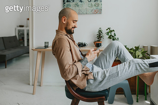 Smiling Young Man Talking to his Friends on Social Media while Casually Sitting in his Apartment - gettyimageskorea