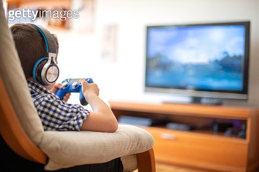 Boy Playing on console with Videogames joystick - gettyimageskorea