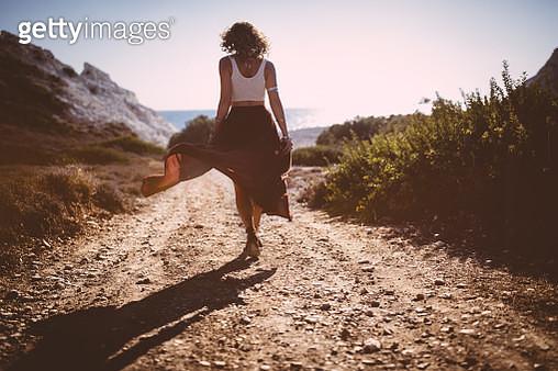 Bohemian girl in skirt and crop top walking in nature - gettyimageskorea