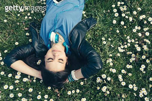Teenage girl lying down in the grass - gettyimageskorea