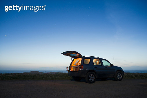 Sports utility vehicle parked on field against clear sky during dusk - gettyimageskorea