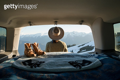 Rear view of female hiker looking at snowcapped mountains while standing outside sports utility vehicle - gettyimageskorea